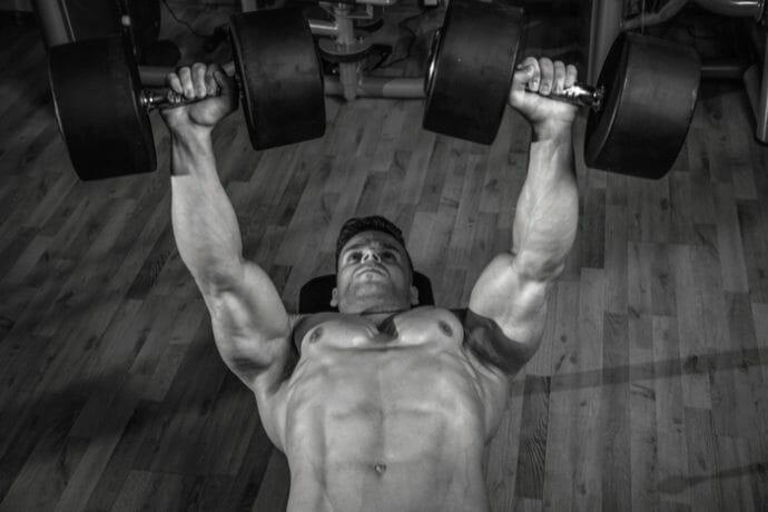 body builder bench-pressing heavy dumbbells