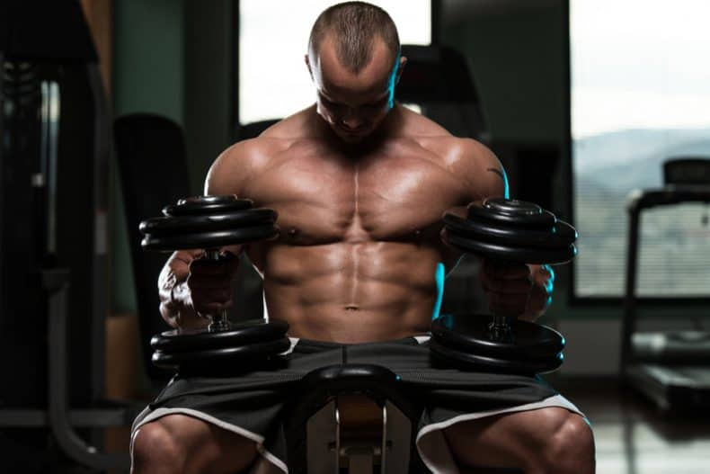 bodybuilding sitting on adjustable weight bench with dumbbells