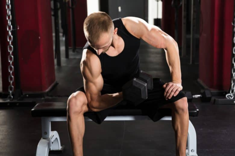 bodybuilder sitting on flat utility weight bench