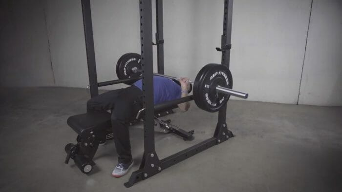 man performing bench press inside rack on rep fitness adjustable weight bench