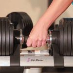 woman taking adjustable dumbbell from stand