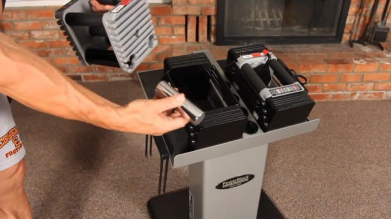 man cganging adjustable weight pins inside powerblock dumbbell