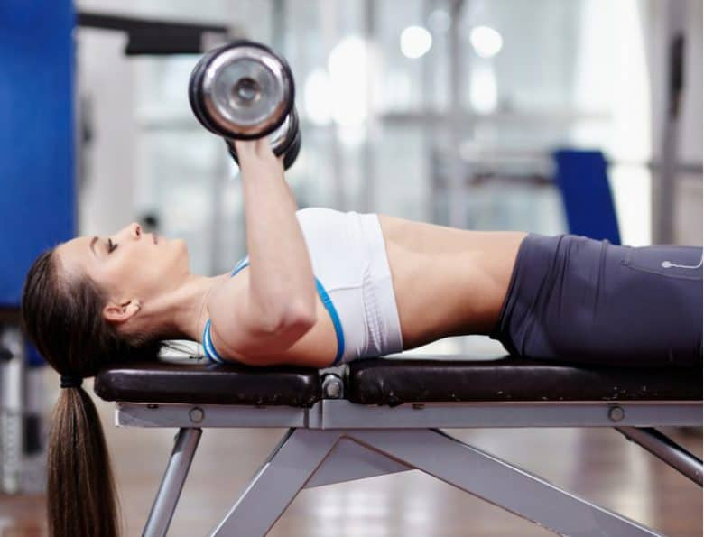 woman laying on bench doing a dumbbell bench press