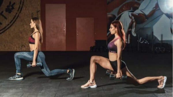 2 women doing lunges with dumbbells