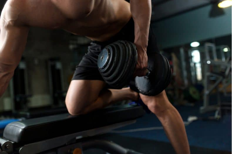body building performing kneeling dumbbell row