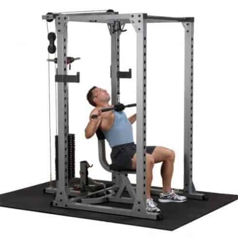 bodybuilder performing lat pulldown inside body solid power rack