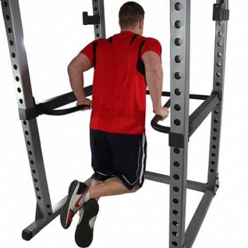 bodyduilder performing dips inside power rack