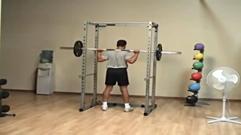 body builder squatting using power rack