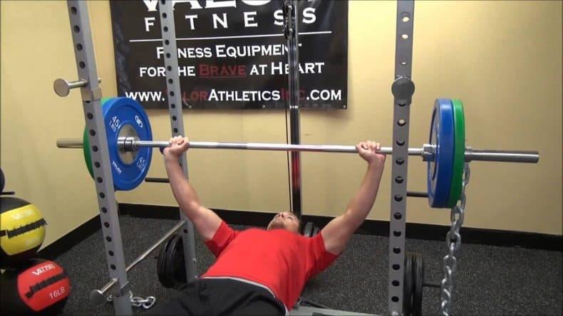 man bench pressing inside Valor fitness db 7 power rack