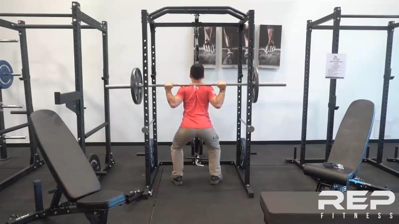 man squatting inside rep power rack