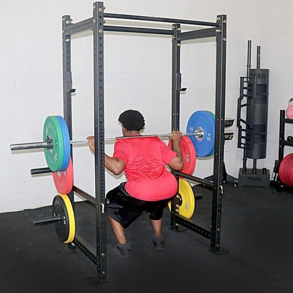 bodybuilder performing squats inside t3 short rack