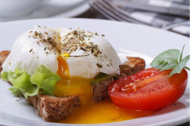 poached egg on toast with tomato on white plate