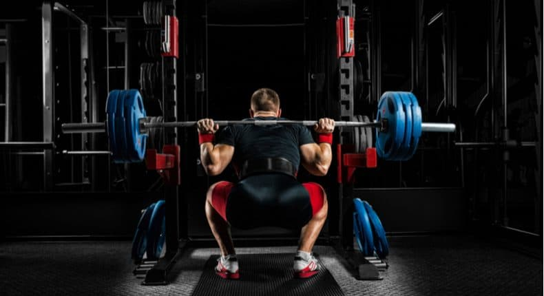 man squatting with nike weight lifting belt