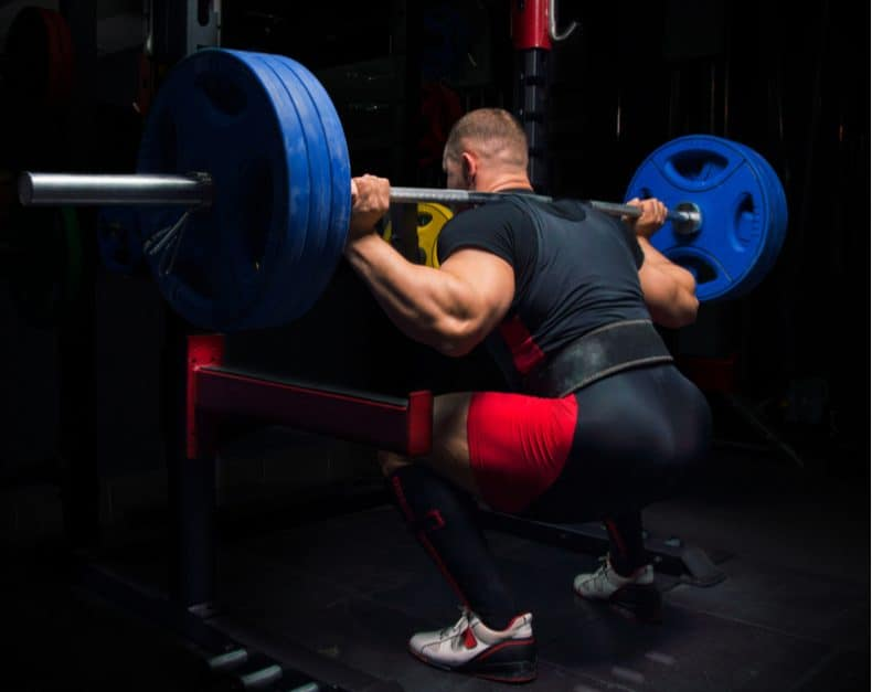 power lifter squatting heavy barbell