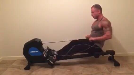 man rowing on merax rowing machine in his home