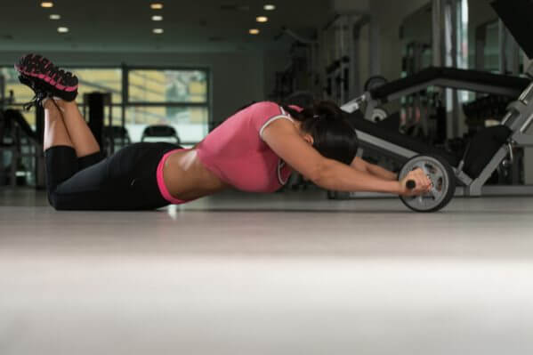 female athlete performing rollouts with best ab roller