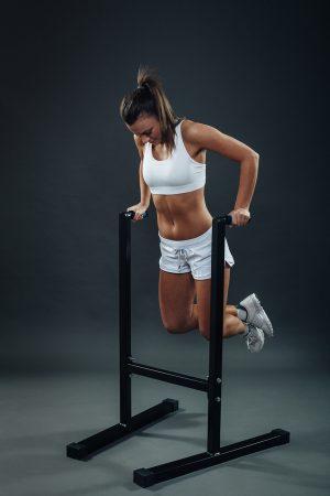 Woman performing tricep dips on dip bars