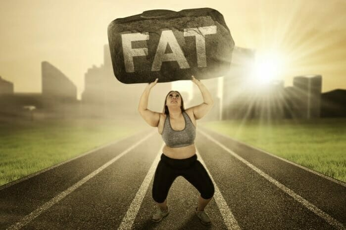 overweight woman lifting a rock labeled fat