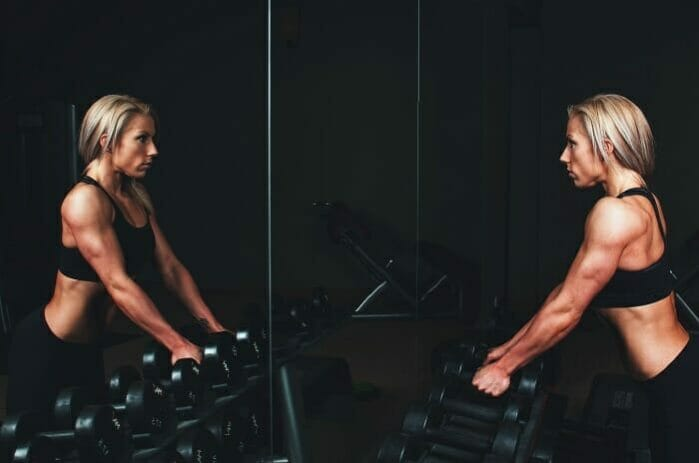 muscular women looking at mirror getting ready to work out