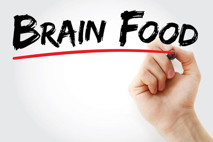 mans hand writing brain food on clear screen