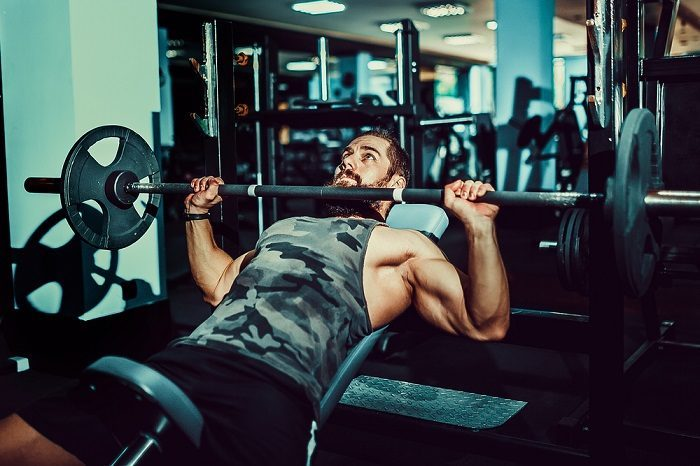bearded man performing inclined barbell press