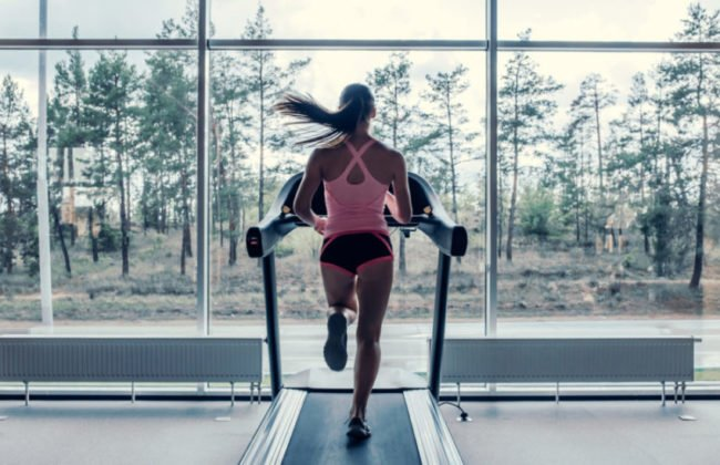 fit woman running on a treadmill in front of the window
