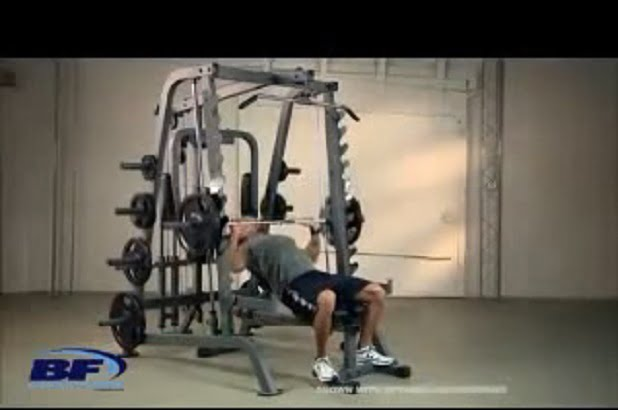 man performing bench press on body solid series 7 smith machine