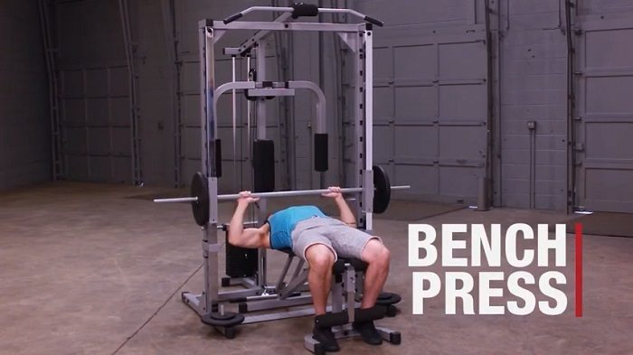 man performing bench press on powerline PSM1442XS smith machine