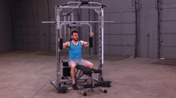 man using body-solid pec dec on smith machine
