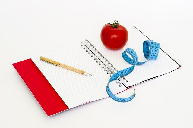 diary, tomato, measuring tape and a pencil