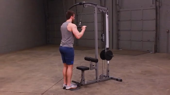 man performing tricep push-downs on body solid glm83 lat machine