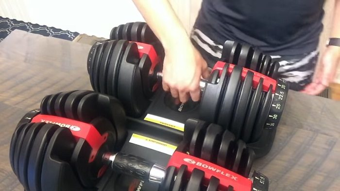 man holding one of two bowflex dumbbells 552