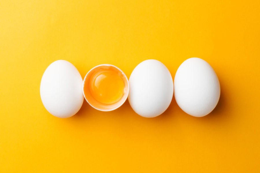three whole eggs and one broken with yolk showing aligned on a yellow surface