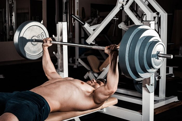 man lifting heavy barbell on flat weight bench