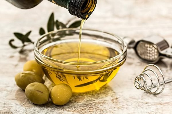 a few olives next to a round clear bowl filled with olive oil