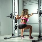 woman performing squats on home smith machine