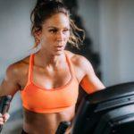woman exercising on home gym elliptical machine