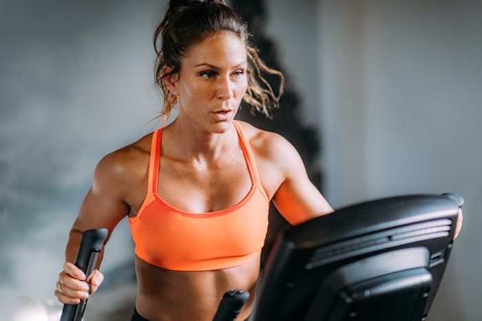 woman exercising on elliptical machine in her home