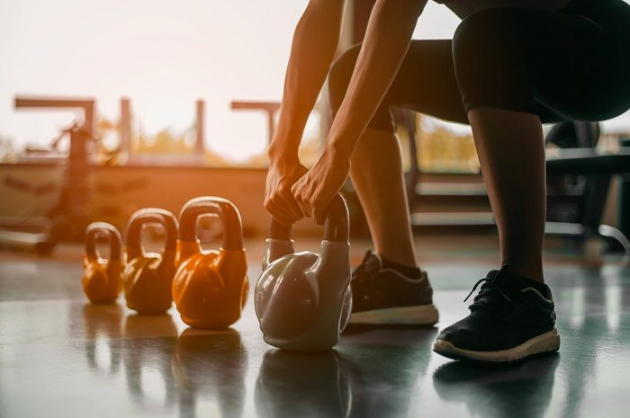 woman workoing out with kettlebells in gym