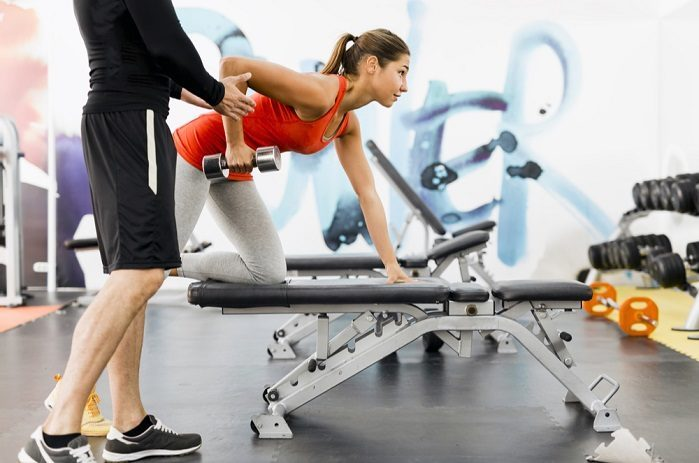 woman performing dumbbell rows with personal trainer in her local gym