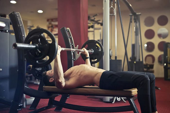 fit man doing bench press in a gym