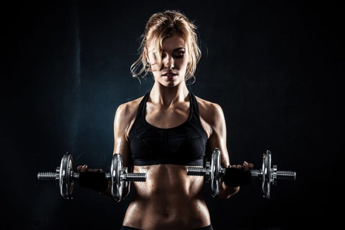fit blond woman holding weights showing 6 pack abs