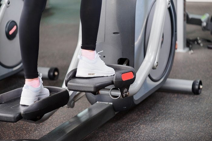 woman walking on elliptical trainer in a gym