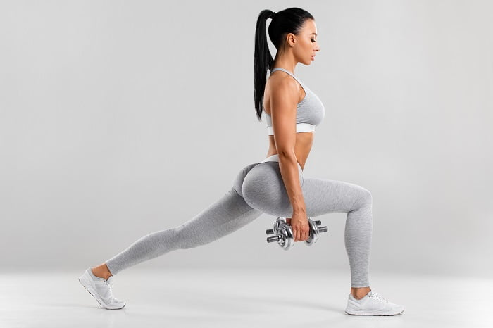 fit woman in grey outfit doing best quads workout holding dumbells