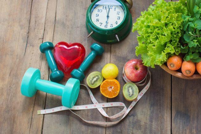 Measuring tape, dumbbells, fruit and vegetables representing ways to get slim