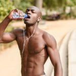fit black man drinking water from a bottle