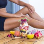 image representing healthy diet and fitness a young woman sitting next to the jar with fruit