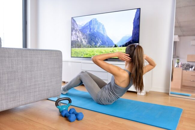 woman working out at home in front of the tv