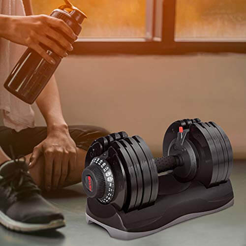 man sitting next to Mermax adjustable dumbbell after workout