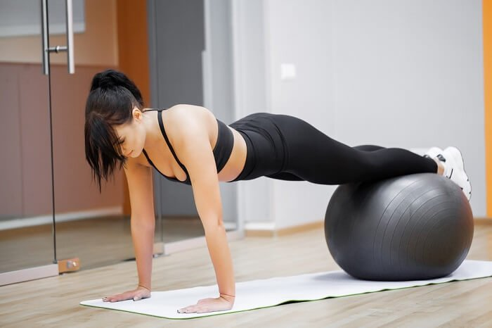 woman doing exercises for lateral abdominal muscles using a pilates ball